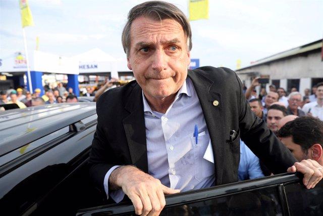 FILE PHOTO: Presidential candidate Jair Bolsonaro leaves an agribusiness fair in