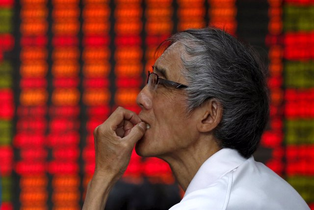An investor looks at an electronic board showing stock information at a brokerag