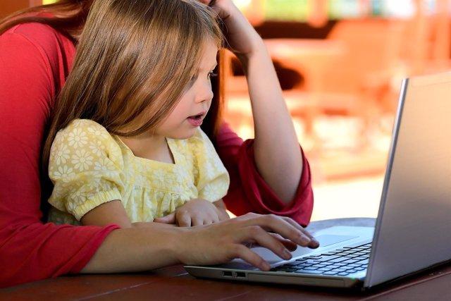 Niña y familia utilizando ordenador