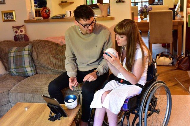 Una mujer con discapacidad utiliza un nuevo aparato para aumtar su destreza.