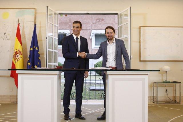 El presidente del Gobierno, Pedro Sánchez, firma con el secretario general de Podemos, Pablo Iglesias, su acuerdo para los presupuestos