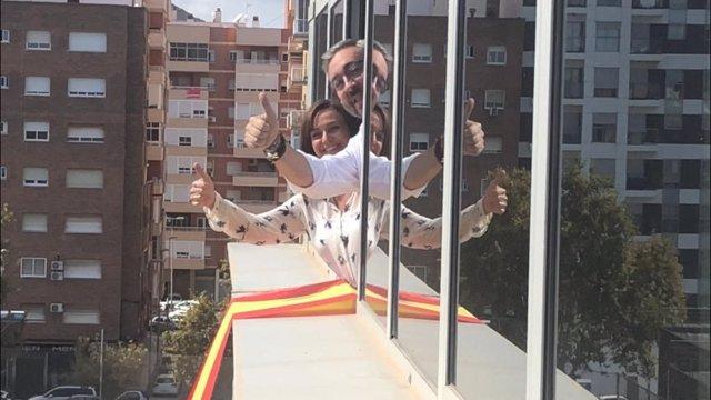 Momento en el que PP cuelga bandera de España en fachada Asamblea