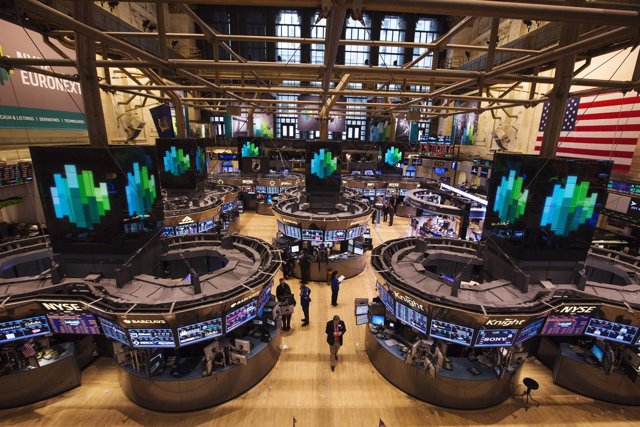 Traders work after the closing bell on the floor of the New York Stock Exchange,