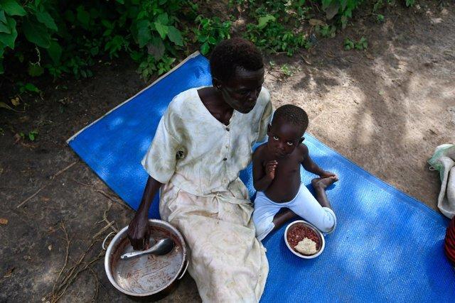 Una mujer y su hijo, refugiados de Sudán del Sur, comen en Palorinya