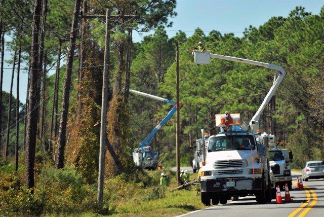 Reparan postes de luz en Florida tras el paso del huracán Michael.