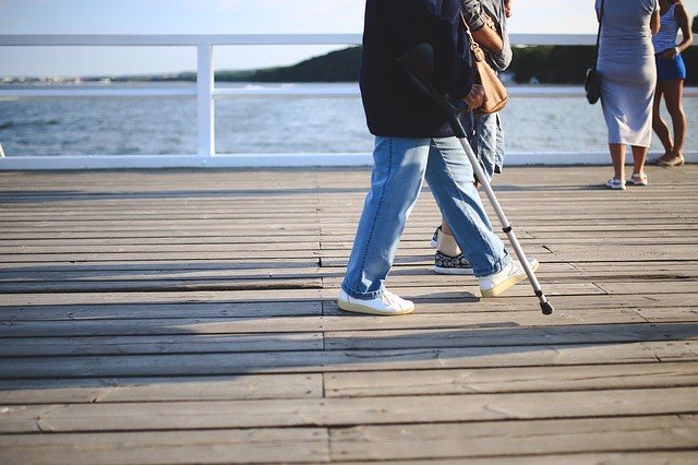 Mujer anda con una muleta, osteoporosis