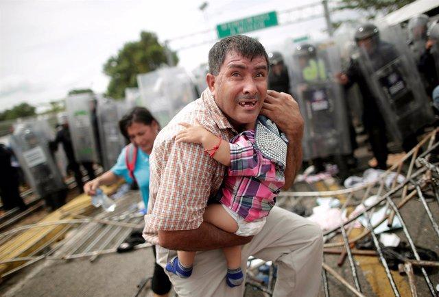 Foto de un migrante hondureño protegiendo a un niño
