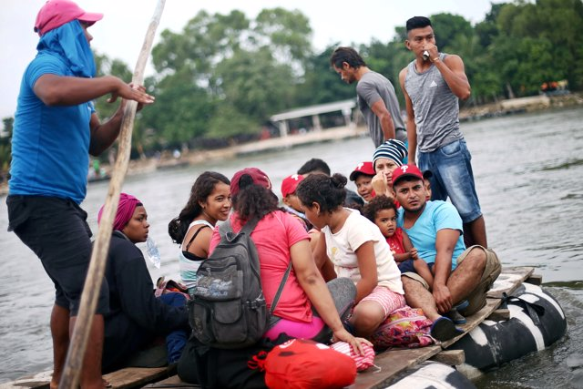 Honduran migrants, part of a caravan trying to reach the U.S., cross the Suchiat