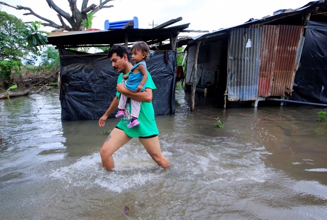 A local resident holds his daughter, as he walks through floodwaters after heavy