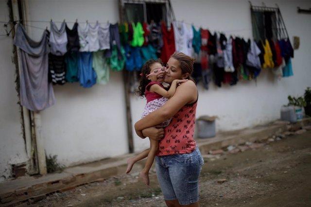 Una mujer con su hija, que padece micocefalia debido al virus zika, en Brasil.