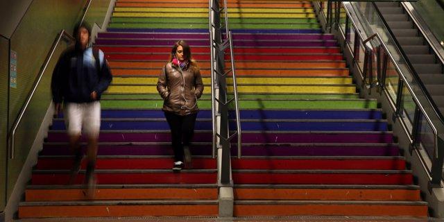 Un hombre y una mujer en unas escaleras con la bandera LGBT, Buenos Aires