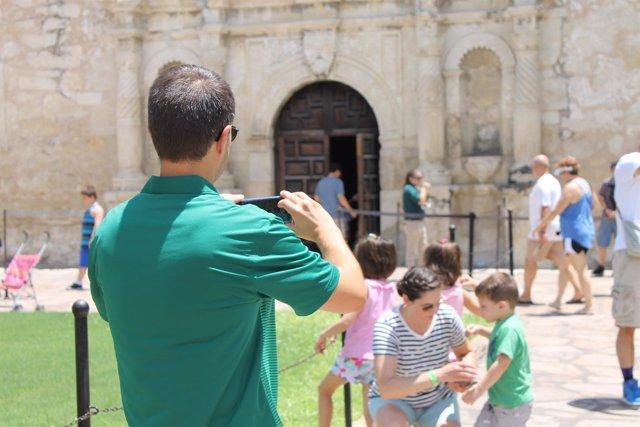 Padre haciendo foto con móvil a madre e hijo