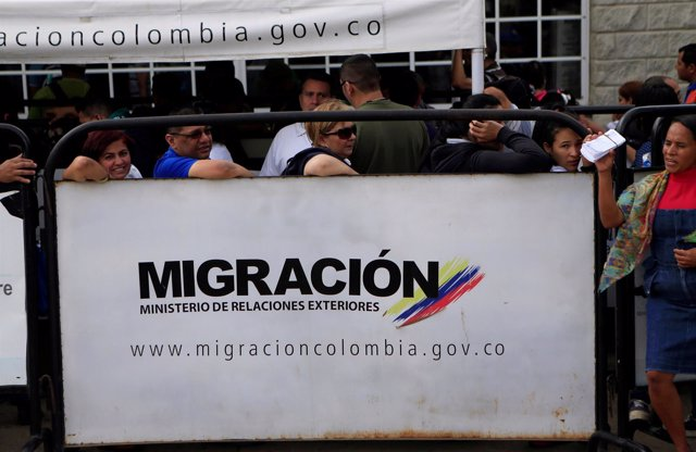 Venezuelans stand in line, outside a migration office, at the border between Ven