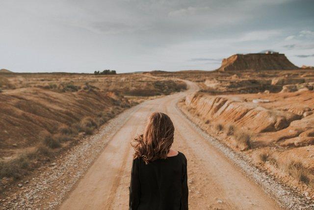 Mujer de espaldas, pelo largo, decisión, desierto