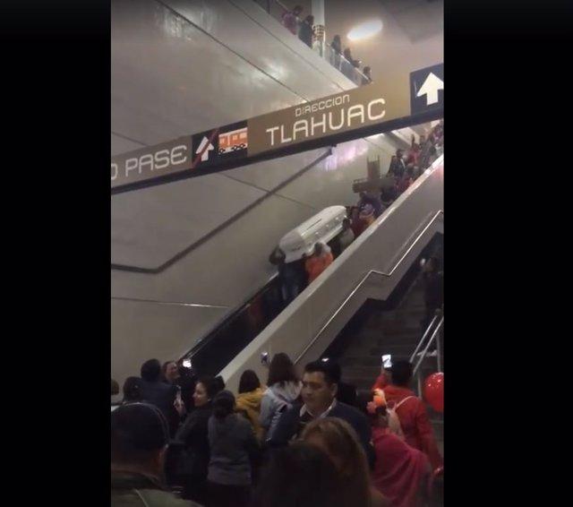 Un grupo de personas caragando un ataúd en el metro de Ciudad de México