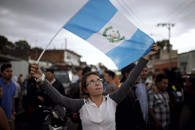 A woman holds a Guatemalan flag and celebrates as Guatemala's former President O