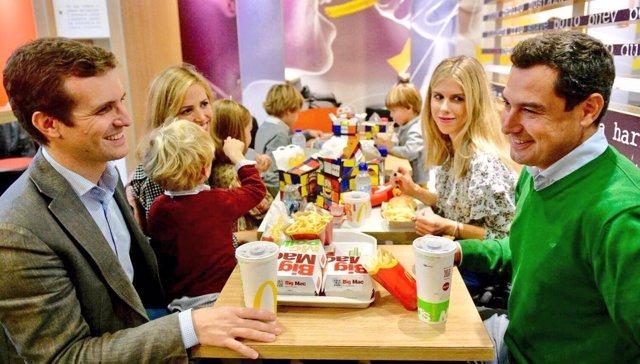 Pablo Casado y Juanma Moreno, con sus familias, en una hamburguesería