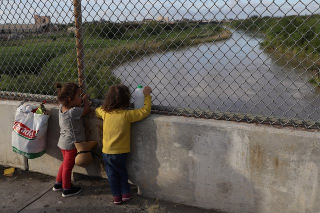 Honduran girls look out at the Rio Grande on the Mexican side of the Brownsville
