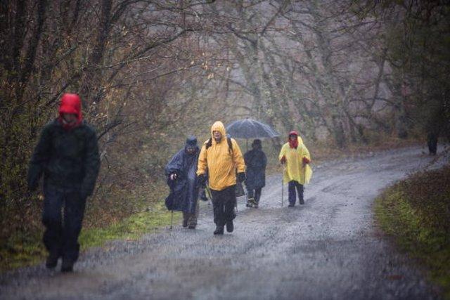 Peregrinos andando con choiva no Camiño de Santiago.