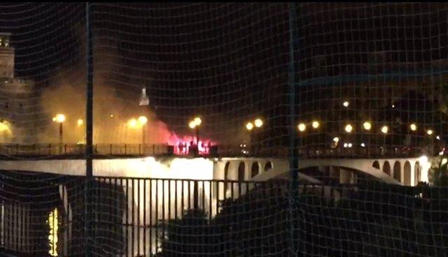 Aficionados del Betis y del Milán con bengalas en el puente de San Telmo