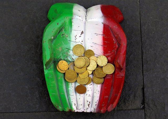 Monedas de euro en unas manos con la bandera de Italia