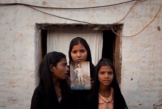Las hijas de la cristiana paquistaní Asia Bibi posan con una foto de su madre