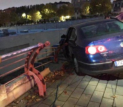 Abandona su coche empotrado contra una valla y a punto de caer