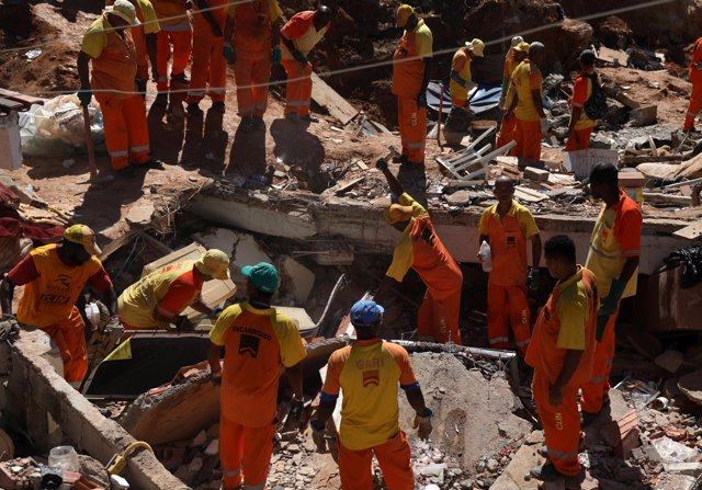 Rescue workers remove debris at the site of a landslide at the Boa Esperanca slu