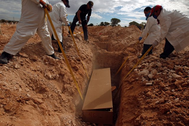 Forensic workers bury an unclaimed body in a mass grave at San Rafael cemetery i
