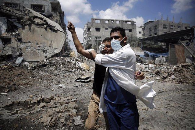 AUn médico ayuda a un palestino duramte la ofensiva isarelí sobre Gaza