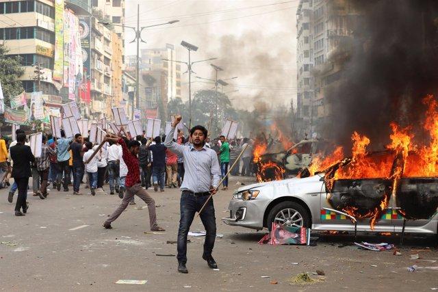 Activistas del partido opositor BNP queman vehículos policiales en Dacca