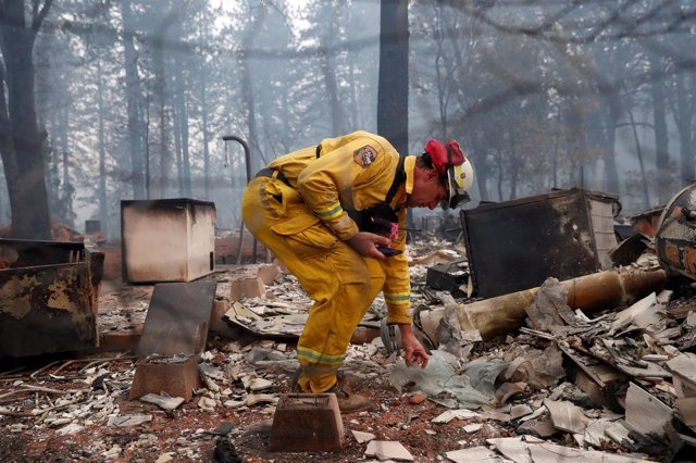 Un bombero inspecciona una zona afectada por los incendios en California