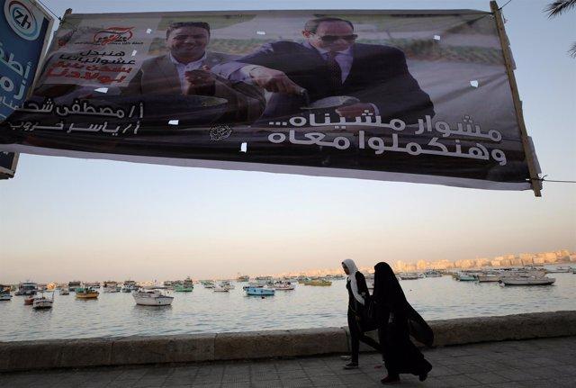 Mujeres bajo un cartel de Abdelfatá al Sisi