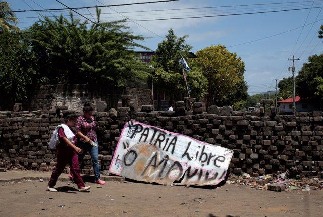 Mujeres junto a una pancarta tras las manifestaciones en Nicaragua