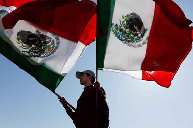 A man waves Mexican flags, during a protest against migrants who are part of a c