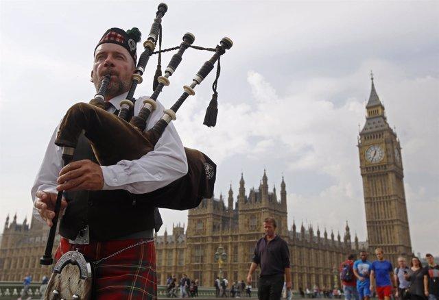 Hombre toca la gaita frente al Parlamento británico