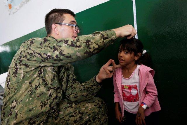 Una niña venezolana recibe la atención de un miembro del buque USNS Comfort