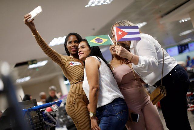 Cuban doctors take a selfie as they return to their home, after criticism by Bra