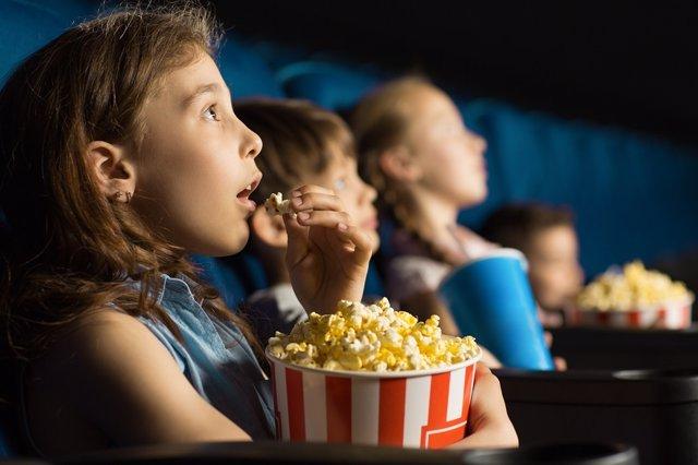 Niños comiendo palomitas en el cine