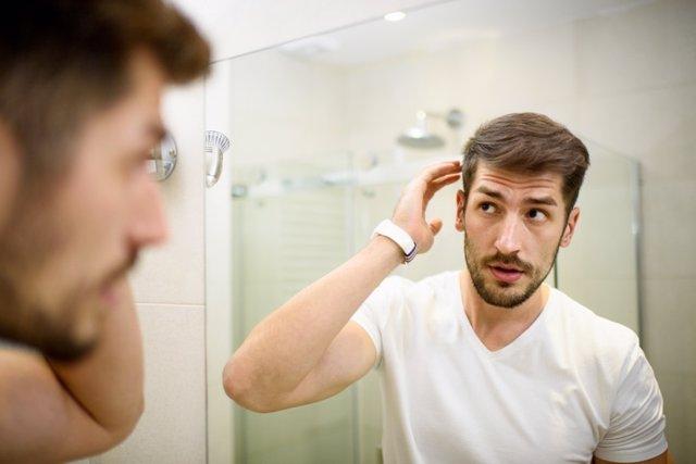 Hombre con barba mirando al espejo en el baño