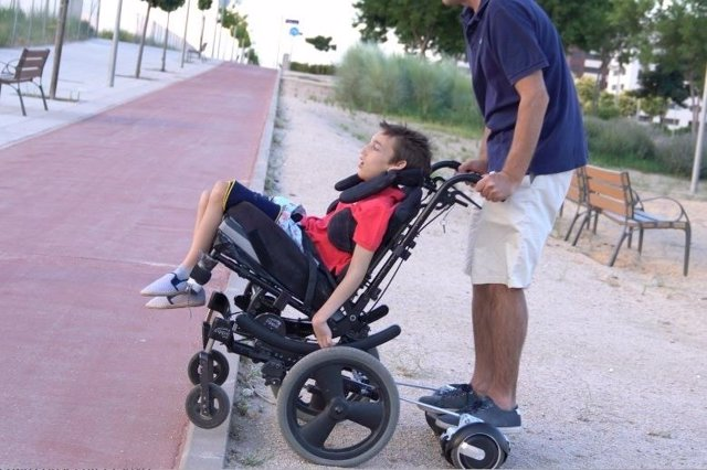 José, paseando a su hijo José, con una silla de ruedas mejorada
