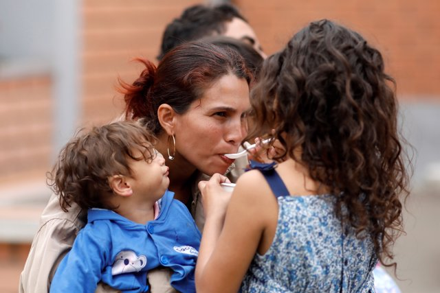 A Venezuelan migrant child feeds her mother during the inauguration of a tempora
