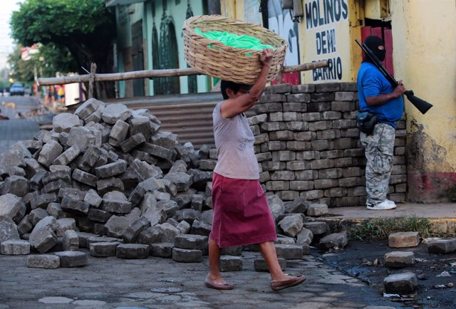 Una mujer camina ante un hombre armado en Monimbó