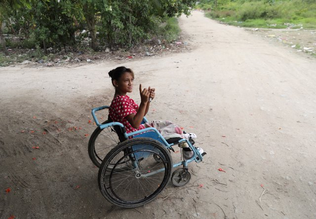 Catherine Ramos, 15, sits in a wheelchair in a street in San Pedro Sula, Hondura
