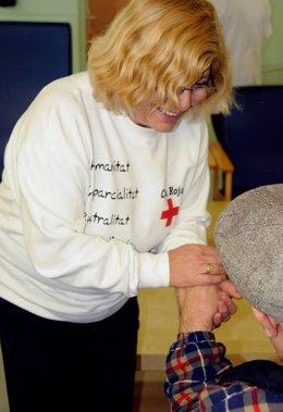 Una voluntària de Creu Roja amb un senyor gran