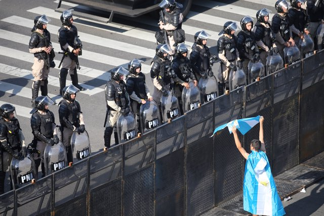 A demonstrator shows the Argentine flag to riot police during the Group 20 summi