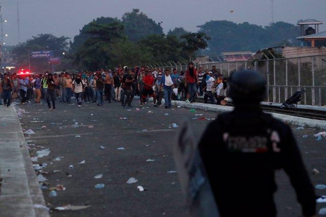 Migrantes tratando de cruzar hasta México frente a policía