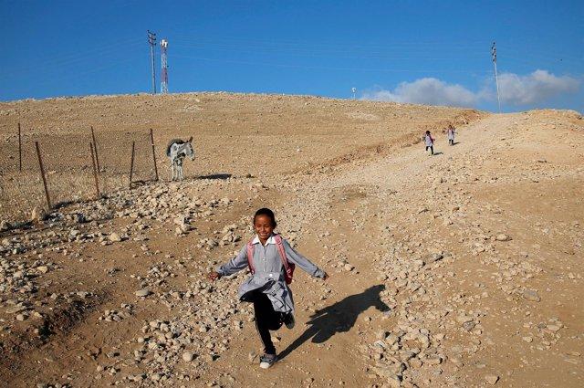 Una niña palestina corre hacia la escuela en Jan al Ahmar