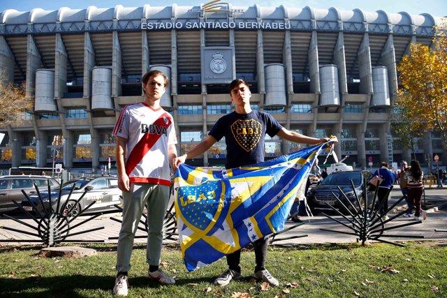 Un hincha del Boca y otro del River posan frente al Bernabéu