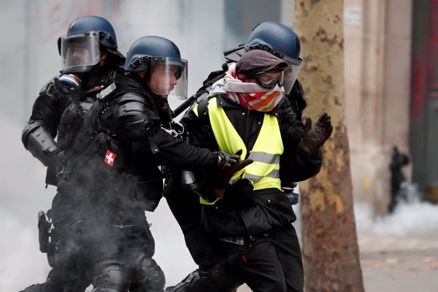 Gendarmes gales detienen a un encapuchado en una protesta de chalecos amarillos